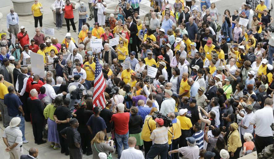Protesters congregate in front of city hall Tuesday, May 26, 2015, in Cleveland. Members of about 40 churches are protesting the acquittal of a white patrolman charged in the deaths of two unarmed black motorists with a march through downtown Cleveland. (AP Photo/Tony Dejak)
