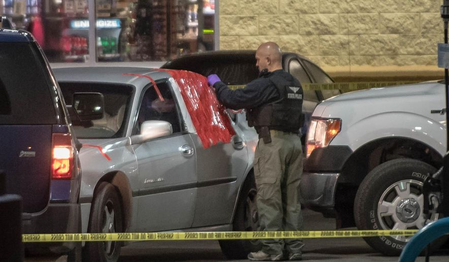 A state police investigator seals off a car near Rio Bravo and Broadway, Tuesday, May 26, 2015, after police took into custody a suspect involved in a fatal shooting against a Rio Rancho officer Monday evening. (Roberto E. Rosales/Albuquerque Journal via AP)