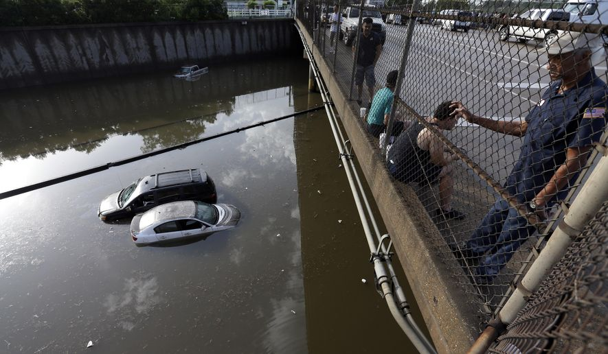 Cars sit in floodwaters along Interstate 45 after heavy overnight rain flooded parts of the highway in Houston, Tuesday, May 26, 2015. Several major highways in the Houston area are closed due to high water. (AP Photo/David J. Phillip)
