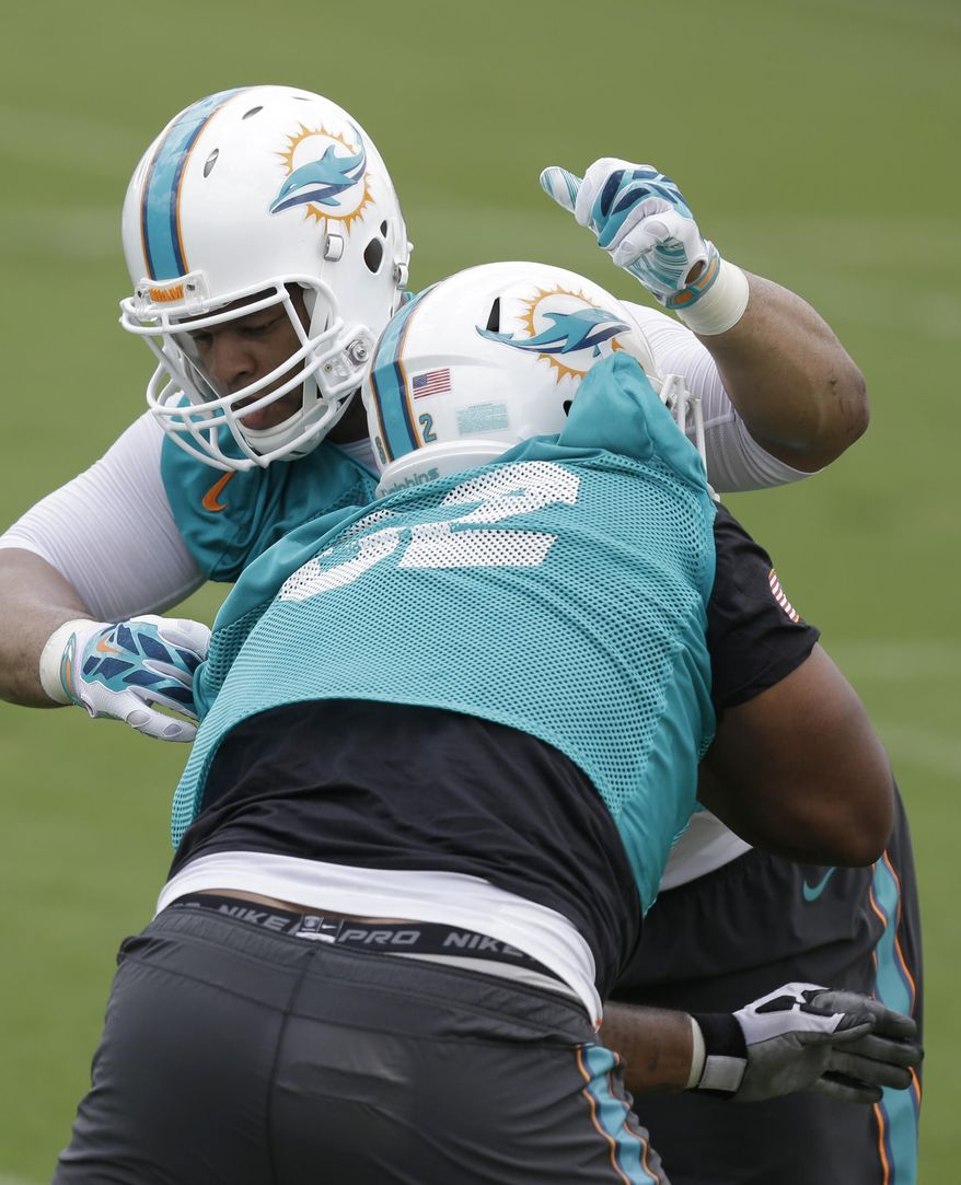 Miami Dolphins defensive tackle Ndamukong Suh, rear, and defensive tackle Deandre Coleman participate in a drill during an NFL football organized team activity, Tuesday, May 26, 2015, at the Dolphins training facility in Davie, Fla. (AP Photo/Wilfredo Lee)