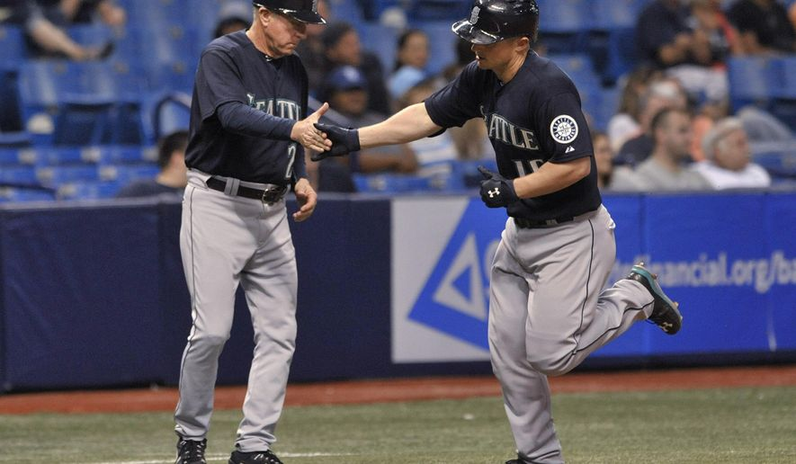 Seattle Mariners third base coach Rich Donnelly, left, congratulates Kyle Seager as he circles the bases after hitting a solo home run off Tampa Bay Rays reliever Brad Box Berger during the 10th inning of a baseball game Tuesday, May 26, 2015, in St. Petersburg, Fla. (AP Photo/Steve Nesius)