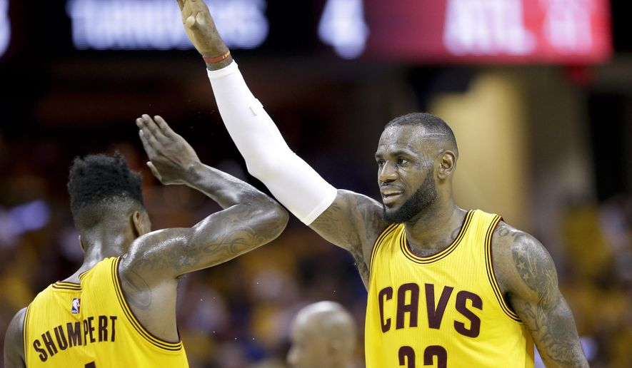 Cleveland Cavaliers forward LeBron James (23) high fives guard Iman Shumpert (4) during a timeout  in the first half of Game 4 of the NBA basketball Eastern Conference Finals against the Atlanta Hawks Tuesday, May 26, 2015, in Cleveland. (AP Photo/Tony Dejak)