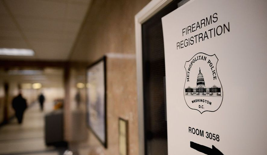 Signs direct people to the office of the Firearms Registration Unit at the District's Metropolitan Police Department headquarters. (Andrew Harnik/The Washington Times)
