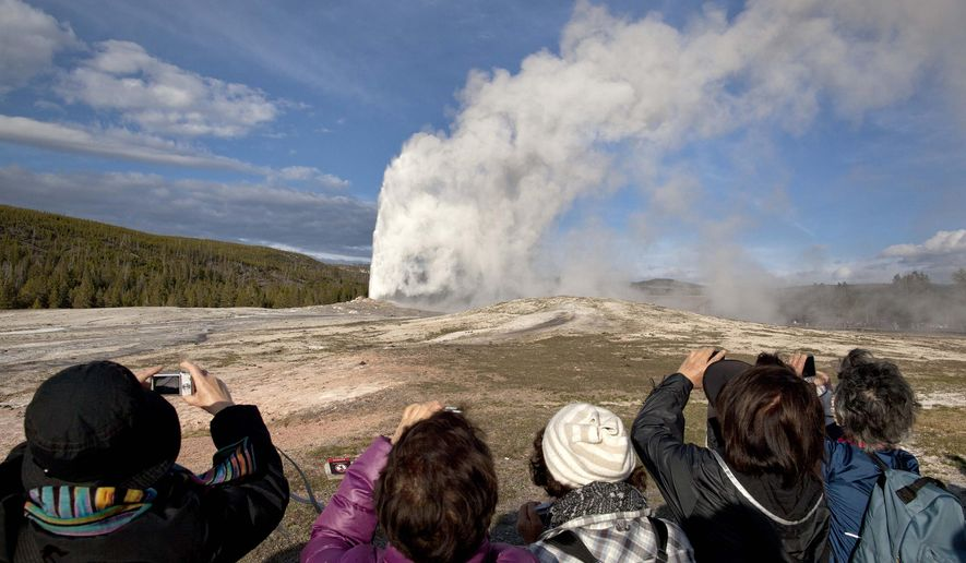 FILE - In this Saturday, May 21, 2011 file photo, tourists photograph Old Faithful erupting on schedule late in the afternoon in Yellowstone National Park, Mont. Lower gas prices and other indicators point to plenty of out-of-state visitors coming to Wyoming to enjoy national parks and other attractions this summer, tourism officials say. (AP Photo/Julie Jacobson, File)
