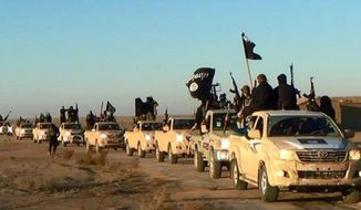 Islamic State group members hold up their weapons and wave its flags on their vehicles in a convoy on a road leading to Iraq, while riding in Raqqa city in Syria. (Associated Press) ** FILE **