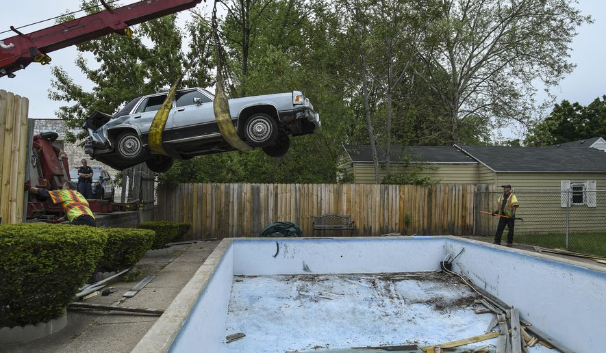 In a Sunday, May 24, 2015 photo, a car is removed from a swimming pool after an elderly woman accidentally drove her vehicle through a fence and into a Wyoming resident's empty pool while at the CVS pharmacy window, off 28th St. in Wyoming, Mich.  Police stated she accidentally went in reverse and that she did not suffer from any major injuries.  (Taylor Ballek/The Grand Rapids Press via AP) ALL LOCAL TELEVISION OUT; LOCAL TELEVISION INTERNET OUT