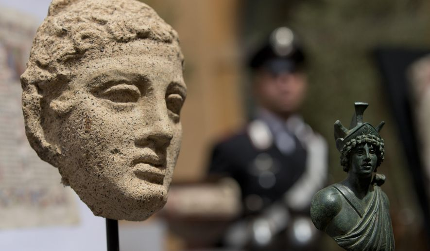 A third century B.C. terracotta head, left, and a second century Roman bronze figure representing Mars, are shown during a press conference in Rome, Tuesday, May 26, 2015. The United States has returned 25 artifacts that were looted from Italy, including Etruscan vases, 1st century frescoes and precious books that had made their way into top-notch U.S. museum, university and private collections. (AP Photo/Alessandra Tarantino)