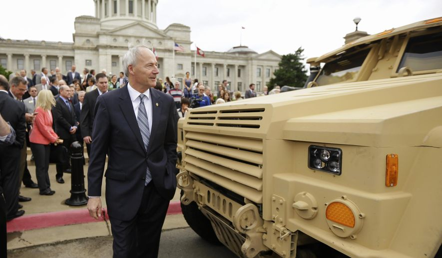 Arkansas Gov. Asa Hutchinson walks by a prototype of a tactical vehicle that will replace the Humvee, parked in front of the Arkansas state Capitol in Little Rock, Ark., Tuesday, May 26, 2015. Hutchinson called the defense project he hopes to lure with an $87 million incentive package being considered by lawmakers this week a golden opportunity for the state. (AP Photo/Danny Johnston)
