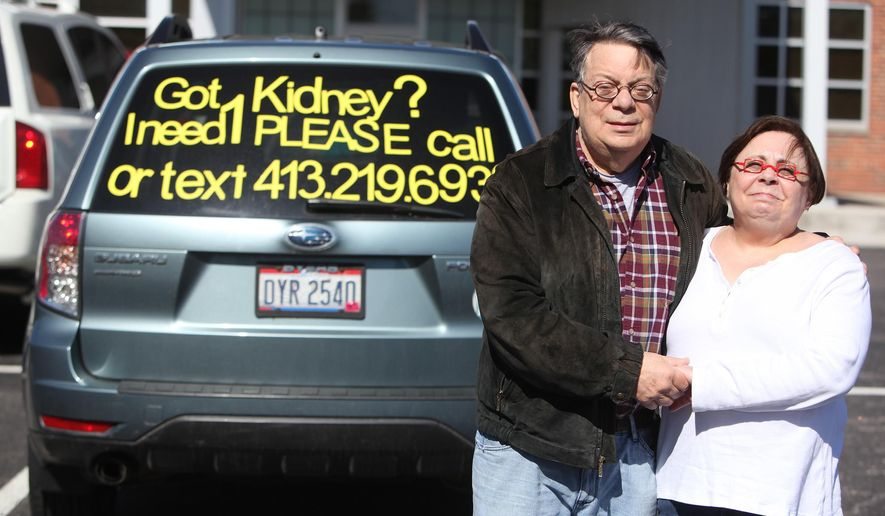 This April 27, 2015 photo shows Neal Raisman and wife Aileen posing for a photo in front of their SUV outside of the Fresenius Medical Care Campus Kidney Center in Columbus, Ohio. The Ohio man in need of a kidney donor is taking his search on the road in unusual fashion, with bright yellow letters taped to the rear window of his vehicle. (Doral Chenoweth III/Columbus Dispatch via AP) MANDATORY CREDIT