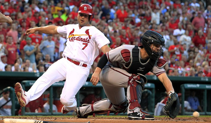 St. Louis Cardinals' Matt Holliday, left, scores as Arizona Diamondbacks catcher Tuffy Gosewisch handles the throw during the first inning of a baseball game Tuesday, May 26, 2015, in St. Louis. (AP Photo/Jeff Roberson)