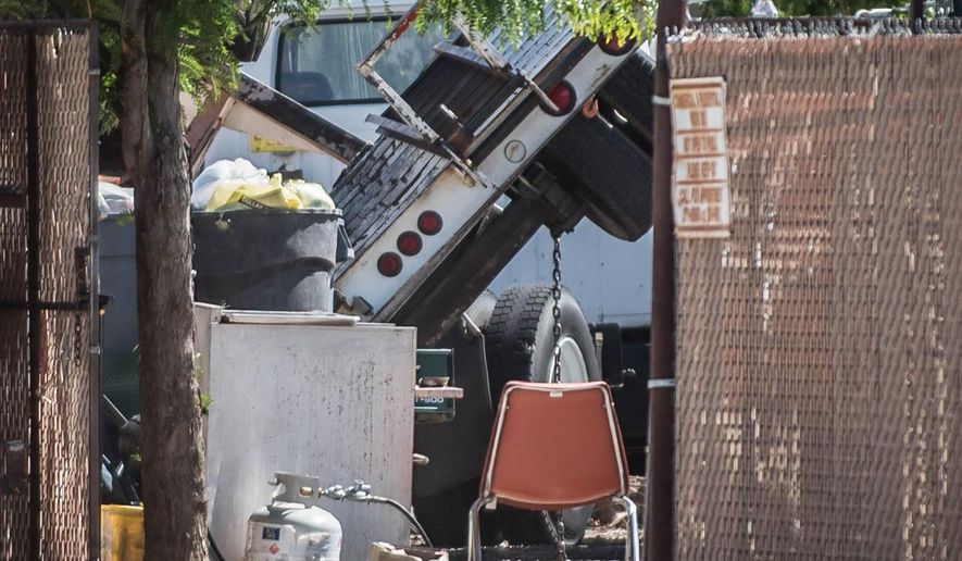 This May 24, 2015 photo shows the scene of a cherry picker accident in Albuquerque, N.M. The deadly accident happened as a man was giving the neighborhood kids a demonstration of the elevated lift, authorities said. (Roberto E. Rosales/The Albuquerque Journal via AP)