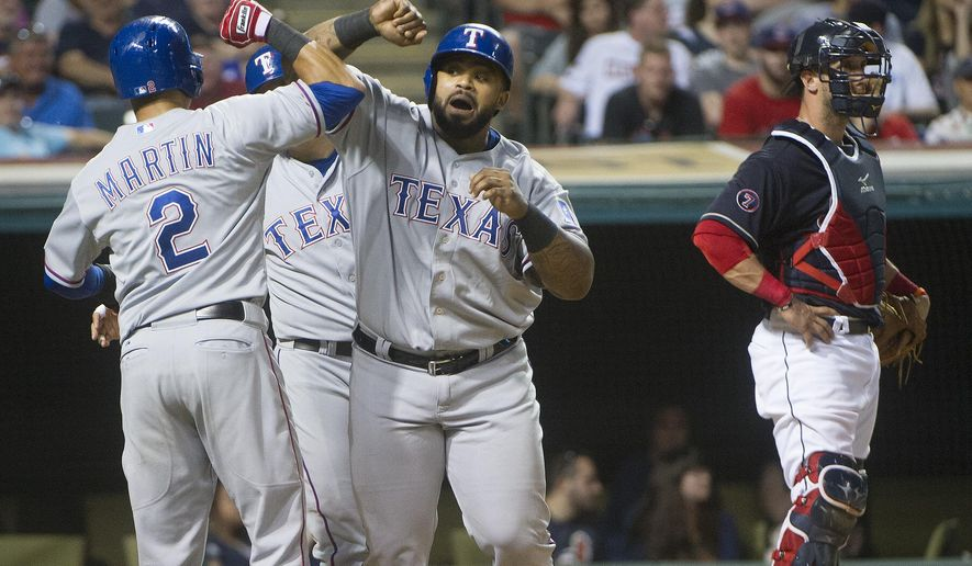 Texas Rangers' Prince Fielder is greeted at home plate by Lenoys Martin (2) and Shin-Soo Choo, after hitting a  three-run home run off Cleveland Indians' Danny Salazar during the fifth inning of a baseball game in Cleveland, Tuesday, May 26, 2015. Indians' Yan Gomes stands at right. (AP Photo/Phil Long)