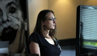 In this May 21, 2015, photo, Christina Blache sits in her living room during an interview with The Associated Press, in Northglenn, Colo. Blache, who was shot through both legs with an assault rifle when James Holmes opened fire in a packed movie theater in Aurora, Colo., in 2012, says that testifying in the Holmes trial has been both cathartic and re-traumatizing. (AP Photo/Brennan Linsley)