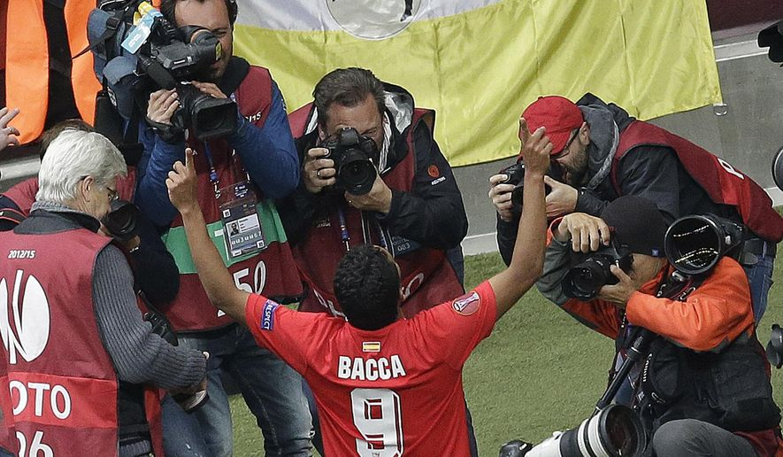 Sevilla's Carlos Bacca celebrates surrounded by photographers after scoring during the final of the soccer Europa League between FC Dnipro Dnipropetrovsk and Sevilla FC at the National Stadium in Warsaw, Poland, Wednesday, May 27, 2015. (AP Photo/Michael Sohn)