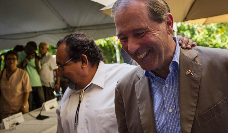 U.S. Senator Tom Udall, right, walks with U.S. senator Raul Grijalba, left, after a press conference in Havana, Cuba, Wednesday, May 27, 2015. Udall, a New Mexico Democrat who led a four-member Democratic congressional delegation to Cuba, all supporters of lifting the embargo on Cuba, said there appears to be growing momentum to removing at least elements of it, such as the ban on travel. (AP Photo/Ramon Espinosa)