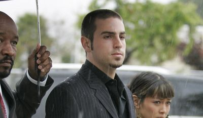 In this May 5, 2005, file photo, defense witness for the Michael Jackson child molestation trial, Wade Robson, arrives for court with an unidentified woman and a member of Jackson's entourage holding an umbrella in the rain at the Santa Barbara County Courthouse in Santa Maria, Calif. (AP Photo/Mark J. Terrill, Pool, File)