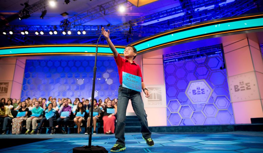 Kasey Torres, 10, of San Angelo, Texas, reaches up for the microphone as he takes the stage during 2015 Scripps National Spelling Bee, Wednesday, May 27, 2015, in Oxon Hill, Md. (AP Photo/Andrew Harnik)
