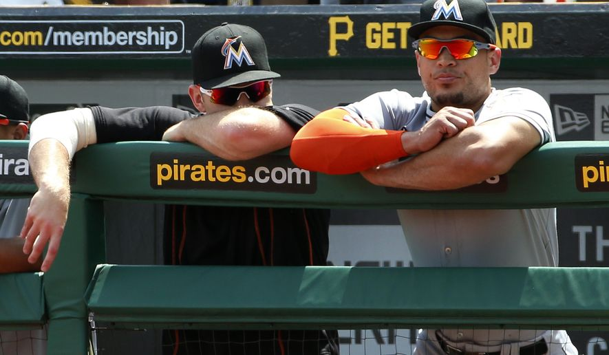 Miami Marlins starting pitcher David Phelps, left, and Giancarlo Stanton stand in the dugout during the ninth inning of a 5-2 loss to the Pittsburgh Pirates in a baseball game in Pittsburgh, Wednesday, May 27, 2015. (AP Photo/Gene J. Puskar)