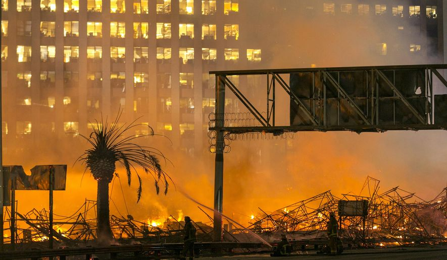 FILE - In this early Monday, Dec. 8, 2014, file photo, Los Angeles firefighters battle a fire at an apartment building under construction next to the Harbor Freeway (Interstate 110) Freeway in Los Angeles. The fire gutted the 1.3 million-square-foot Da Vinci complex. A law enforcement official says a man has been arrested for allegedly causing a massive inferno that destroyed an unfinished apartment building and damaged adjacent office towers in downtown Los Angeles. Damage was estimated at $20 million to $30 million. No one was hurt. (AP Photo/Damian Dovarganes, File)