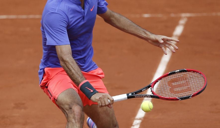 Switzerland's Roger Federer returns the ball to Spain's Marcel Granollers during their second round match of the French Open tennis tournament at the Roland Garros stadium, Wednesday, May 27, 2015 in Paris. (AP Photo/Christophe Ena)