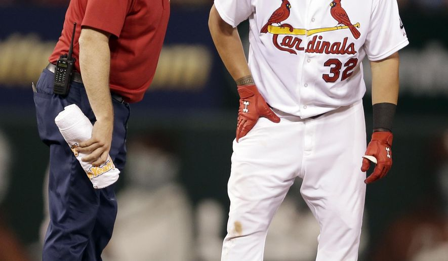 St. Louis Cardinals' Matt Adams, right, is checked on by Cardinals trainer Chris Conroy after being injured during the fifth inning of a baseball game against the Arizona Diamondbacks on Tuesday, May 26, 2015, in St. Louis. Adams left the game after injuring his right leg while running out a double. (AP Photo/Jeff Roberson)