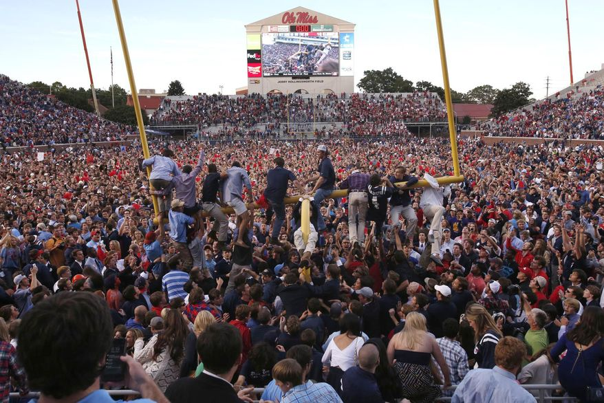 FILE - In this Oct. 4, 2014, file photo, Mississippi fans gather on the field, while a few climb onto a goal post, after Mississippi defeated Alabama 23-17 in an NCAA college football game in Oxford, Miss. The Southeastern Conference has been fining teams for a decade for allowing fans to rush fields and courts. Now, the league appears ready to significantly raise the penalty. (Robert Sutton/The Tuscaloosa News via AP) MANDATORY CREDIT