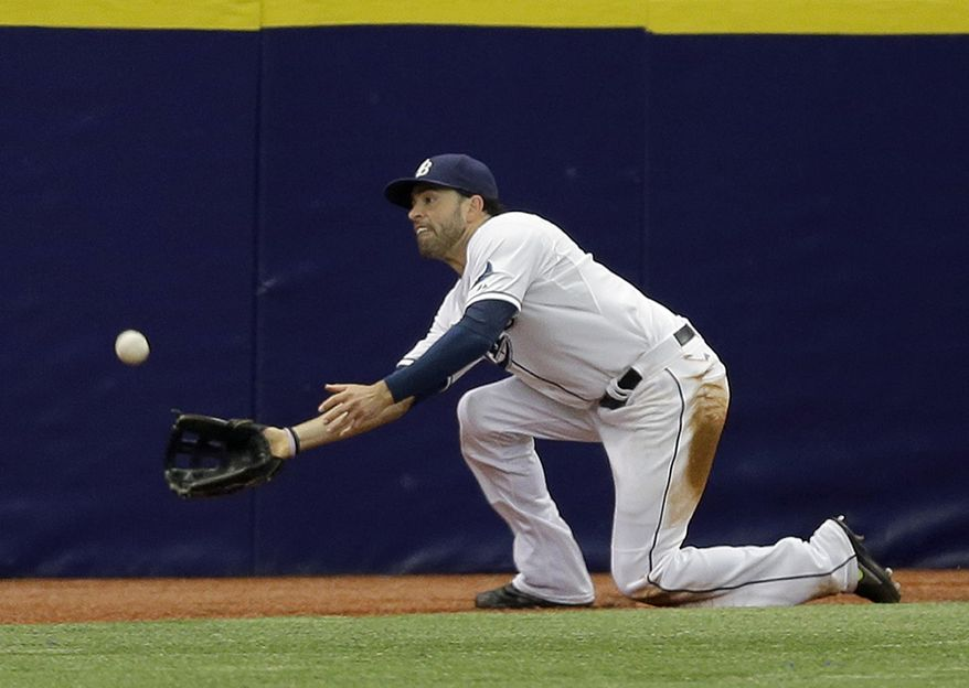 Tampa Bay Rays left fielder David DeJesus prepares to make a sliding catch on a fly ball by Seattle Mariners' Seth Smith during the sixth inning of a baseball game Wednesday, May 27, 2015, in St. Petersburg, Fla.  (AP Photo/Chris O'Meara)