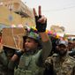 Mourners chant slogans against the Islamic State militant group as they carry the flag-draped coffins of three members of Peace Brigades, a Shiite militia group loyal to Shiite cleric Muqtada al-Sadr who were killed in Ramadi during fighting with Islamic State militants, according to their families, during funeral procession in Najaf, 100 miles (160 kilometers) south of Baghdad, Iraq, Wednesday, May 27, 2015. (AP Photo/ Jaber al-Helo)