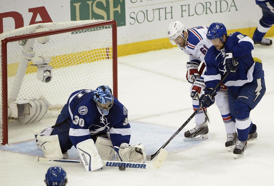 Tampa Bay Lightning goalie Ben Bishop (30) stops a shot as New York Rangers left wing Rick Nash (61) and Tampa Bay Lightning defenseman Anton Stralman (6), of Sweden, look for a rebound during the second period of Game 6 of the Eastern Conference finals in the NHL hockey Stanley Cup playoffs,Tuesday, May 26, 2015, in Tampa, Fla. (AP Photo/Phelan M. Ebenhack)
