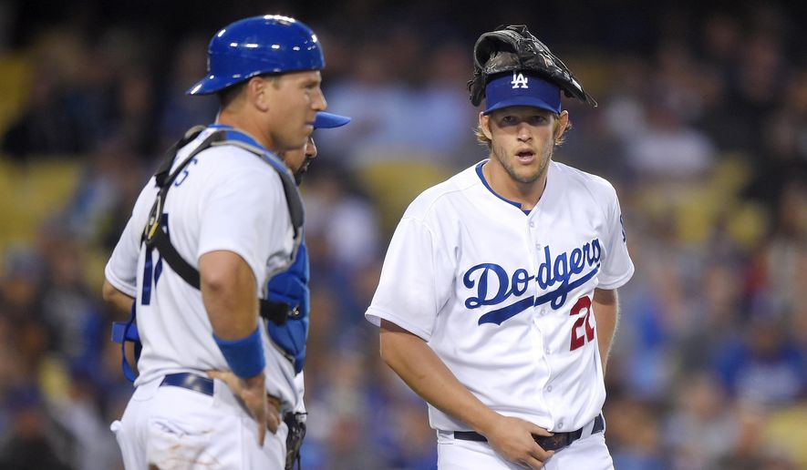 Los Angeles Dodgers starting pitcher Clayton Kershaw, right, and catcher A.J. Ellis wait while the umpires discuss a call during the fourth inning of the Dodgers' baseball game against the Atlanta Braves, Tuesday, May 26, 2015, in Los Angeles. (AP Photo/Mark J. Terrill)