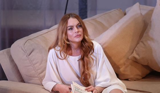 """In this Tuesday, Sept. 30, 2014, file photo, U.S actress Lindsay Lohan performs a scene from the play, """"Speed the Plow,"""" during a photocall at the Playhouse Theatre in central London. (Photo by Joel Ryan/Invision/AP, File)"""