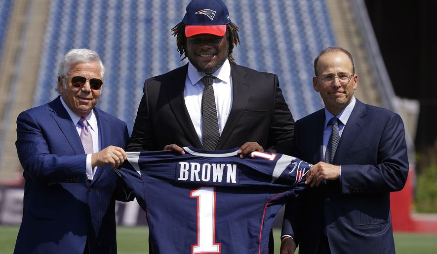 Defensive lineman Malcom Brown, the New England Patriots first round draft pick,  center, poses with Patriots owner Robert Kraft, left, and Patriots president Jonathan Kraft during a media availability at the NFL football team's facility Wednesday, May 27, 2015, in Foxborough, Mass. Brown played his college career at Texas. (AP Photo/Stephan Savoia)