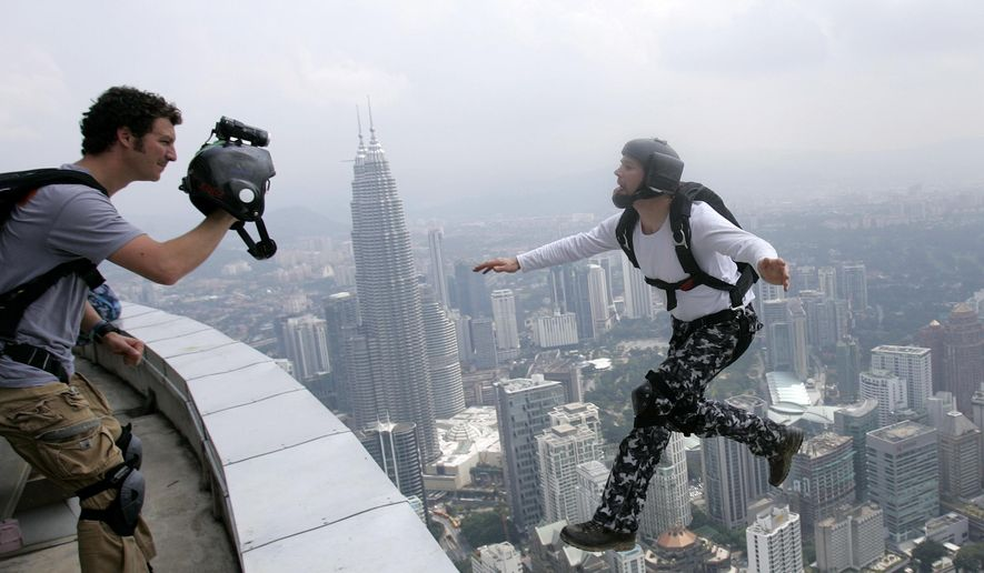 FILE - In this Oct. 24, 2009 file photo, an unidentified BASE jumper leaps from the height of 300 meters off of Malaysia's landmark KL Tower, the 421-meter (1,381-foot) broadcasting tower, in Kuala Lumpur, Malaysia. The sport has come under increased scrutiny in 2015 due to the recent deaths of several BASE jumpers. (AP Photo/Lai Seng Sin, file)