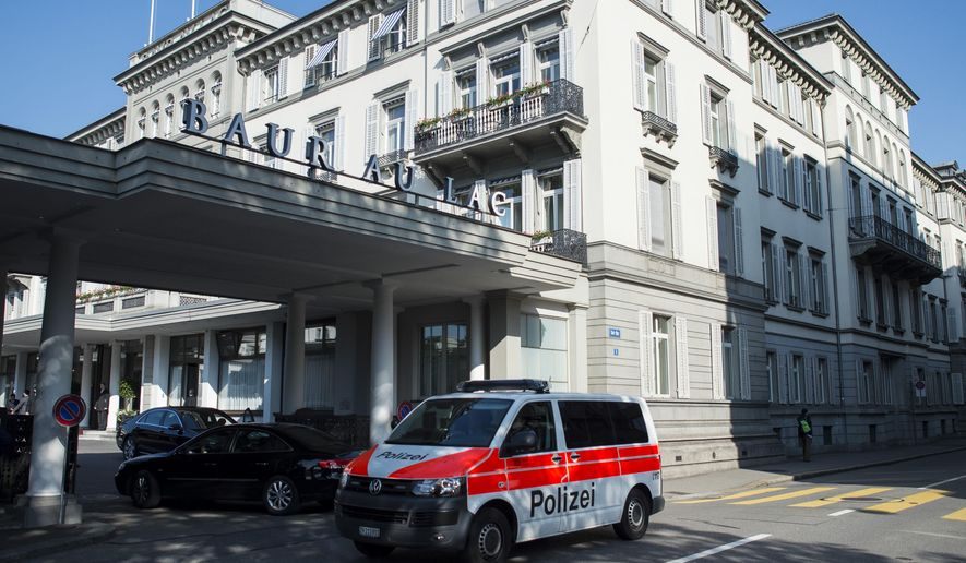 A police vehicle is parked outside of the five-star hotel Baur au Lac in Zurich, Switzerland, Wednesday morning, May 27, 2015. The Swiss Federal Office of Justice said six soccer officials have been arrested and detained pending extradition at  the request of U.S. authorities ahead of the FIFA congress in Zurich. In a statement Wednesday the FOJ said U.S. authorities suspect the officials of having received paid bribes totaling millions of dollars.   (Ennio Leanza/Keystone via AP)