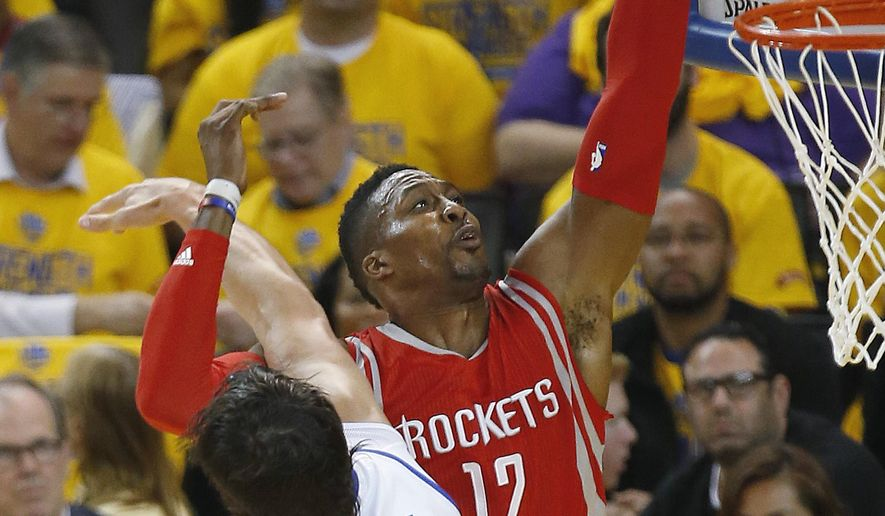 Houston Rockets center Dwight Howard, right, shoots against Golden State Warriors center Andrew Bogut during the first half of Game 5 of the NBA basketball Western Conference finals in Oakland, Calif., Wednesday, May 27, 2015. (AP Photo/Tony Avelar)