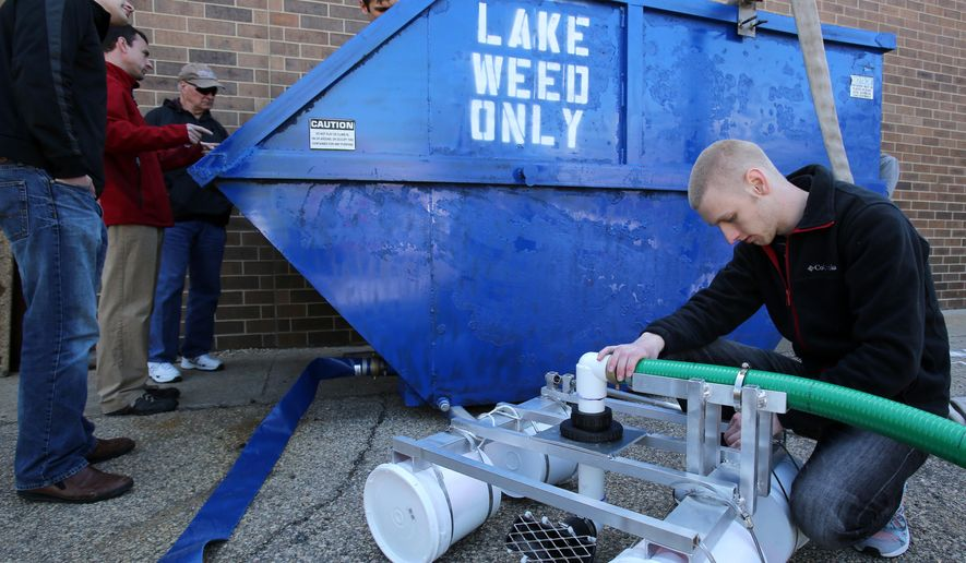 In this photo taken Thursday, May 21, 2015, Madison Area Technical College introduction to engineering student Tyler Lecy, right, checks the pipe clamps on an intake device that is part of a machine created to remove algae from the local lakes, outside the school in Madison, Wis.  (Amber Arnold/Wisconsin State Journal via AP)