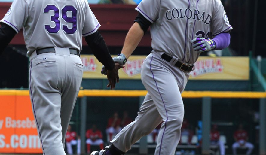 Colorado Rockies' Nolan Arenado, right, is congratulated by third base coach Stu Cole, after hitting a three- run home run against the Cincinnati Reds in the first inning of a baseball game in Cincinnati, Wednesday May 27, 2015.  (AP Photo/Tom Uhlman)