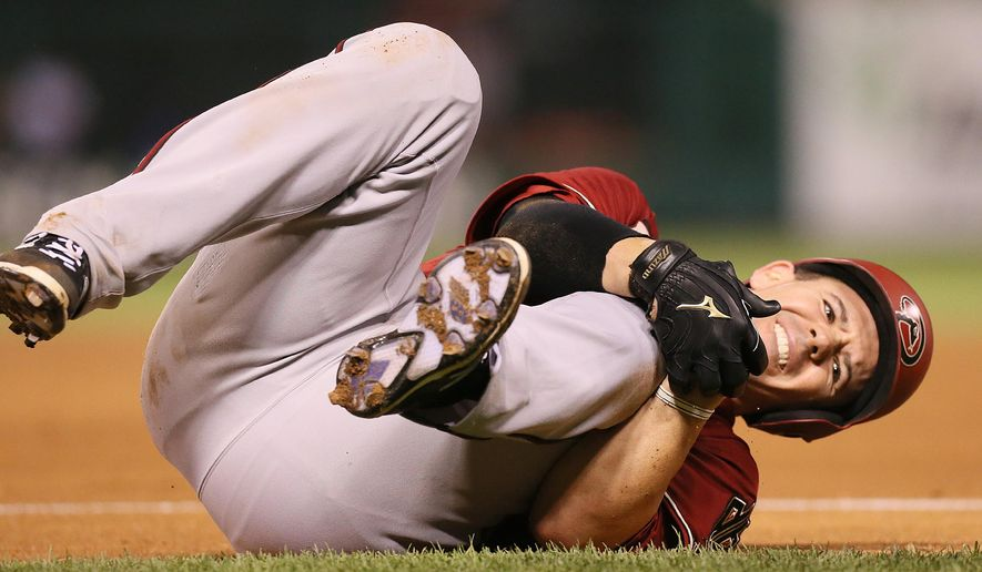 Arizona Diamondbacks' Tuffy Gosewisch clutches his left knee after being injured running out a ground out in sixth inning action during a game between the St. Louis Cardinals and the Arizona Diamondbacks on Wednesday, May 27, 2015, at Busch Stadium in St. Louis. (Chris Lee/St. Louis Post-Dispatch via AP)  EDWARDSVILLE INTELLIGENCER OUT; THE ALTON TELEGRAPH OUT; MANDATORY CREDIT