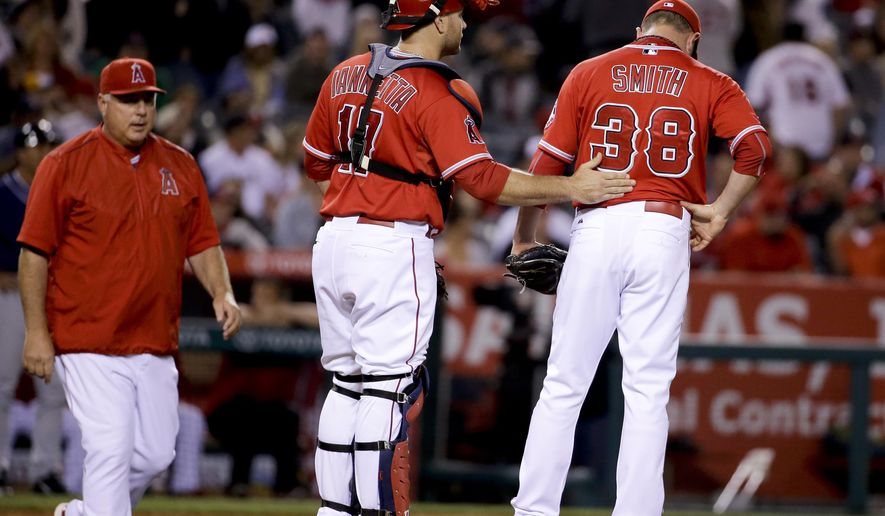 Los Angeles Angels catcher Chris Iannetta, center, consoles relief pitcher Joe Smith after Smith gave up a three-run double to San Diego Padres' Matt Kemp, as manager Mike Scioscia comes out to remove Smith from the baseball game in the 10th inning Anaheim, Calif., Tuesday, May 26, 2015. (AP Photo/Chris Carlson)