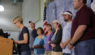 Kellye Burke, left, speaks on behalf of families of the victims of recent severe weather at a news conference, Thursday, May 28, 2015, in Wimberley, Texas. Listening to Burke, background from left, are Mark Combs, Marry Ann Charba, Kim Charba, Cristen Daniel, Justin McComb and and Jeff Schults. The storms and floods in Texas and Oklahoma this week have left at least 21 people dead and at least 10 others missing.  (AP Photo/Eric Gay)