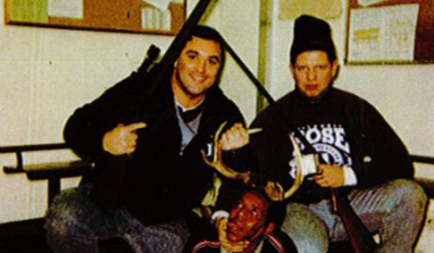 This photo, believed to have been taken between 1999 and 2003, provided by the Cook County Court, in Illinois, shows an image of Chicago Police Officers Jerome Finnigan, left, and Timothy McDermott, right, with an unidentified man, that was made public after McDermott filed a lawsuit in Cook County Circuit Court seeking to rejoin the Chicago Police Department. The Chicago Police Board fired McDermott in October 2014 after finding him guilty of bringing discredit on the department by taking part in the photo, disrespecting or maltreating a person on or off duty, and unlawful or unnecessary use or display of a weapon. (Courtesy of Cook County Court via AP)