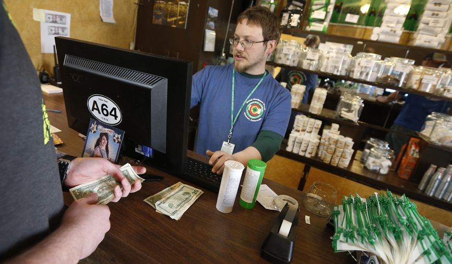 FILE - In this May 8, 2014 file photo, a customer pays cash for retail marijuana at 3D Cannabis Center, in Denver. Three suburban Denver cities are suing Adams County to stop it from collecting taxes from marijuana businesses already being taxed by the cities. At issue is a voter-approved 3 percent sales tax in Adams County that takes effect July 1. (AP Photo/Brennan Linsley, file)