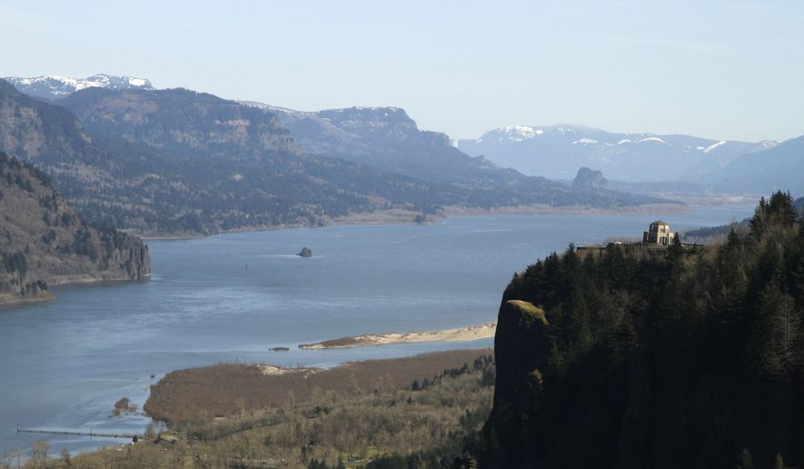 FILE - In this March 7, 2012, file photo, the Columbia River flows past the Vista House on Crown Point at right with Beacon Rock  visible in the distance near Corbett, Ore. The Oregon and Washington departments of Fish and Wildlife have opened a pair of sport salmon fishing opportunities and closed catch-and-keep sturgeon fishing on stretches of the Columbia River upriver from Beacon Rock. (AP Photo/Don Ryan, file)
