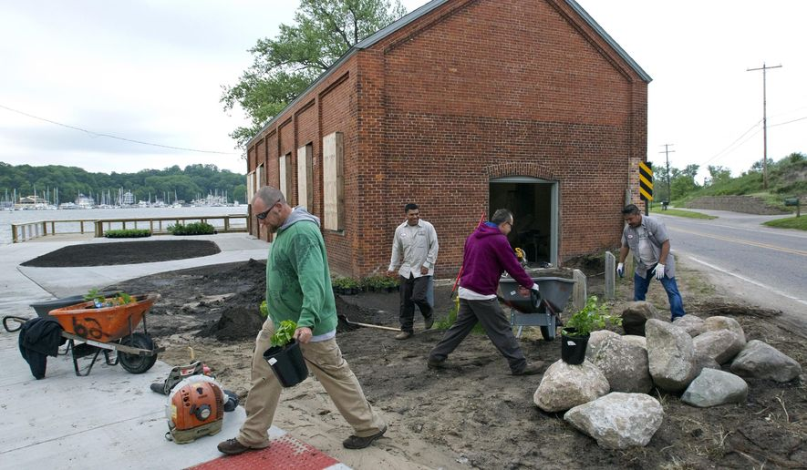 Landscape Design Services workers, from left, Steve Yonker, Juan Gonzalez, Carlos Pedroza and Enrique Alfonso work on the landscaping outside the historic pump house on Ottawa Beach Road,  in Holland, Mich.,  Wednesday, May 27, 2015. Ottawa County Parks and the Historic Ottawa Beach Society are dedicating the preservation of the pump house and hope to continue raising money to establish the structure as a museum.  (Cory Morse/The Grand Rapids Press via AP) ALL LOCAL TELEVISION OUT; LOCAL TELEVISION INTERNET OUT