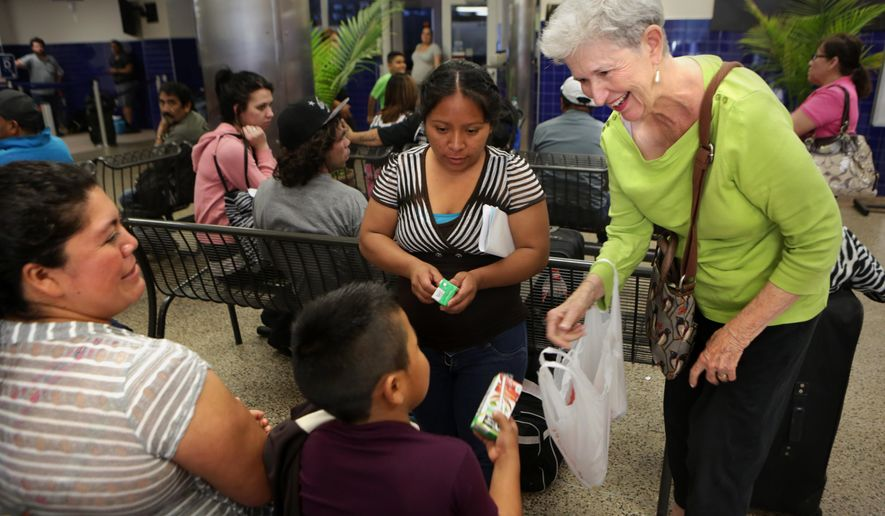 Janice Clayton of Laurel Heights Methodist Church in San Antonio provides drinks to a Guatemalan family on their way from San Antonio to Los Angeles where they have family member on May 20, 2015. (Bob Owen/The San Antonio Express-News via AP)