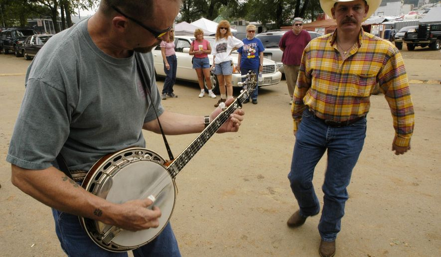 "In August, fiddle players from across the country descend on tiny Galax, Virginia, for the 80th annual Old Fiddler's Convention. This year, the convention runs for a week from Aug. 3 to 8, with the words and music of banjo, mandolin, guitar and autoharp players, folk singing, country and bluegrass bands and ""flatfoot dancing."" (Associated Press)"