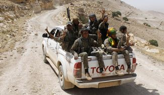 In this photo released on May 20, 2015, provided by the Kurdish fighters of the People's Protection Units (YPG), which has been authenticated based on its contents and other AP reporting, Kurdish fighters of the YPG, flash victory signs as they sit on their pickup on their way to battle against the Islamic State, near Kezwan mountain, northeast Syria. In contrast to the failures of the Iraqi army, in Syria Kurdish fighters are on the march against the Islamic State group, capturing towns and villages in an oil-rich swath of the country's northeast in recent days, under the cover of U.S.-led airstrikes. (The Kurdish fighters of the People's Protection Units via AP)