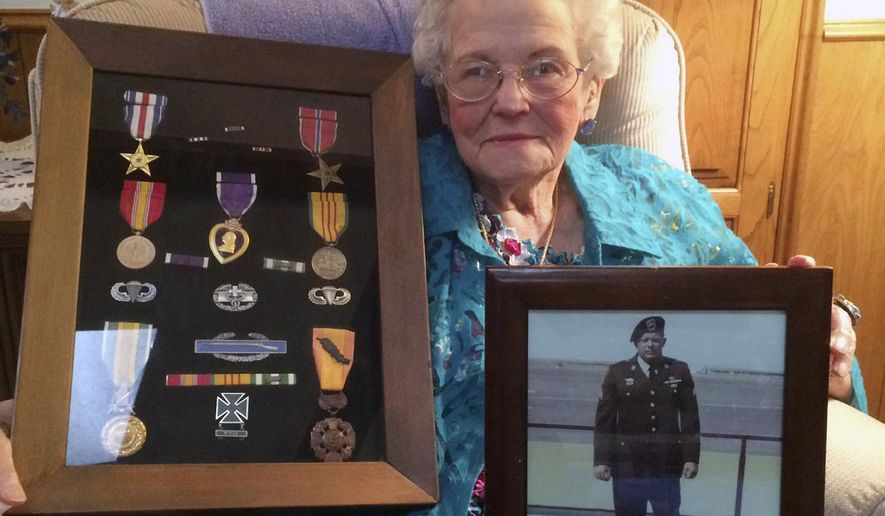 ADVANCE FOR MONDAY JUNE 1 - In this Thursday, May 21, 2015 photo, Oleta Smith of Dumas, Texas, 97, the oldest Gold Star mother in Texas, has found solace from three men who were in Vietnam with her son, Sgt. Warren Smith. Oleta holds her son's picture and display of his war medals. (Jon Mark Beilue/The Amarillo Globe News via AP)
