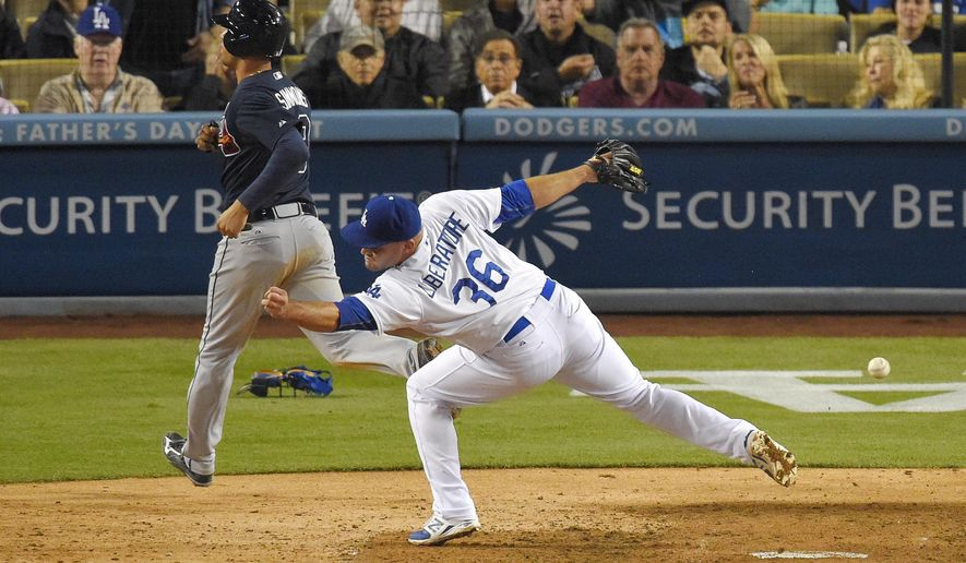 Atlanta Braves' Andrelton Simmons, left, scores on a wild pitch as Los Angeles Dodgers relief pitcher Adam Liberatore misses the throw to the plate during the eighth inning of a baseball game, Wednesday, May 27, 2015, in Los Angeles. (AP Photo/Mark J. Terrill)