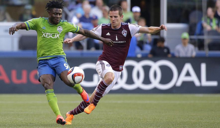 Seattle Sounders' Obafemi Martins, left, is challenged by Colorado Rapids' Sam Cronin, right, in the first half of an MLS soccer match, Wednesday, May 27, 2015, in Seattle. (AP Photo/Ted S. Warren)